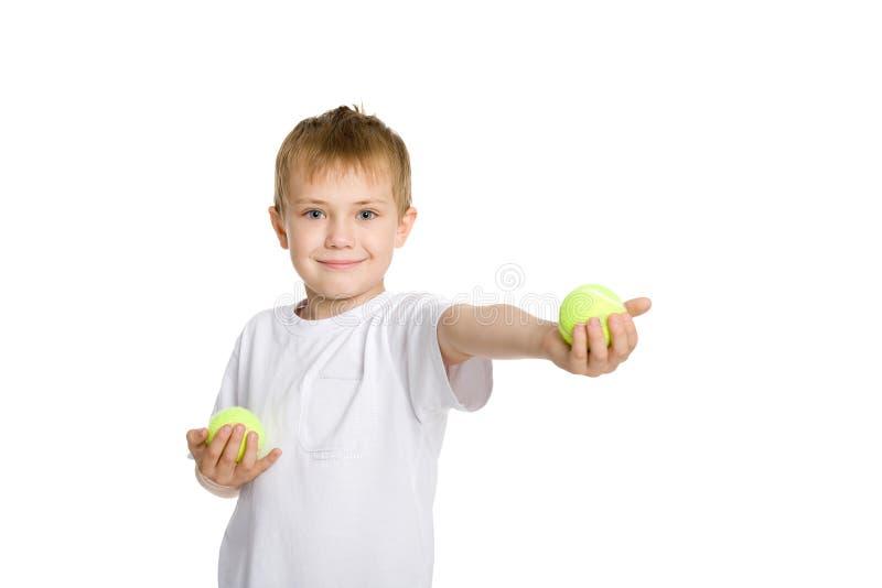 Muchacho que juega en las pelotas de tenis. fotografía de archivo libre de regalías