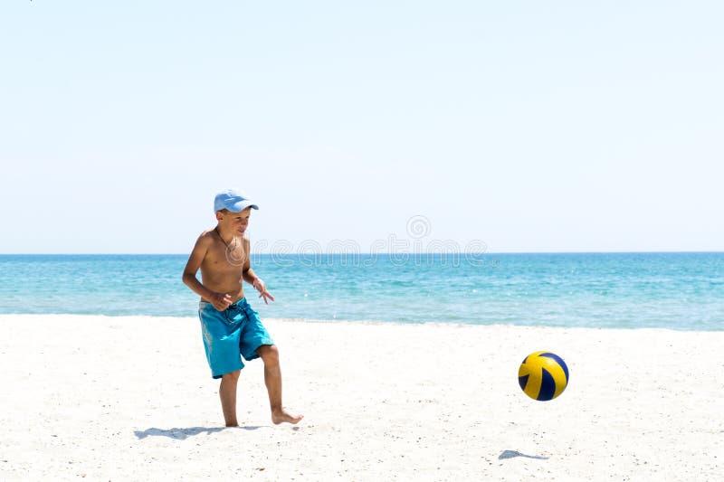 Muchacho que juega a fútbol en la playa imagenes de archivo