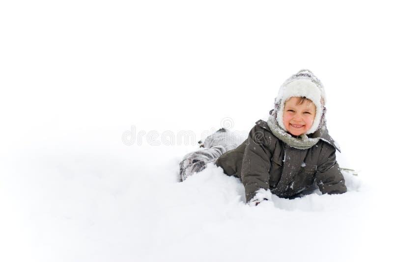 Muchacho que juega feliz en la nieve imagenes de archivo
