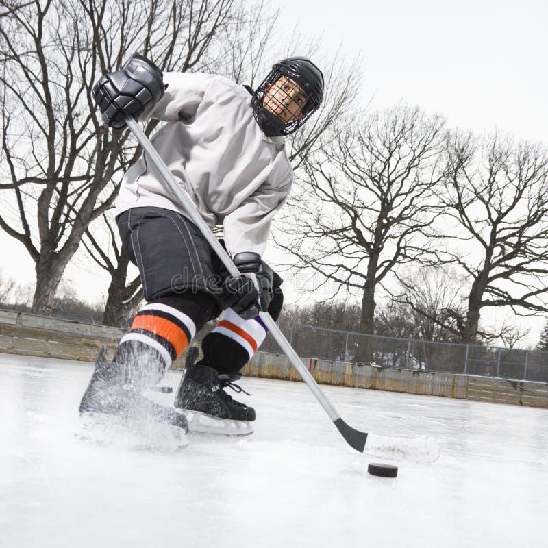 Muchacho que juega a hockey sobre hielo. foto de archivo