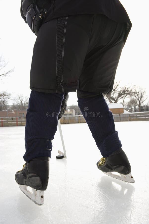 Muchacho que juega a hockey sobre hielo. imagenes de archivo
