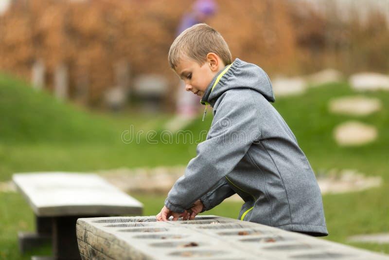 Muchacho que juega mancala consigo mismo imagenes de archivo