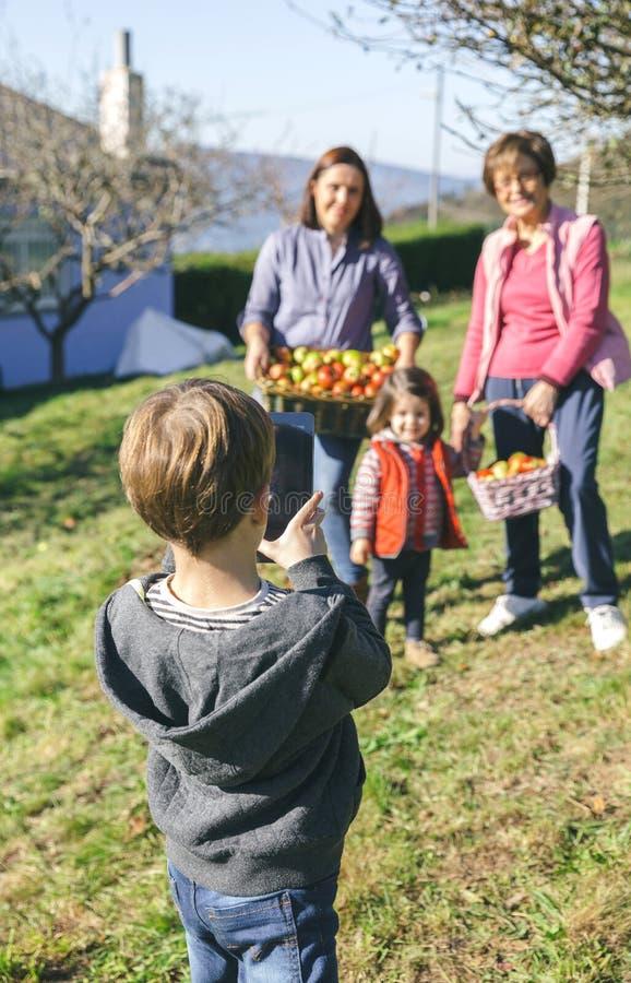 Muchacho que lleva la foto la familia con las manzanas en cesta fotos de archivo libres de regalías