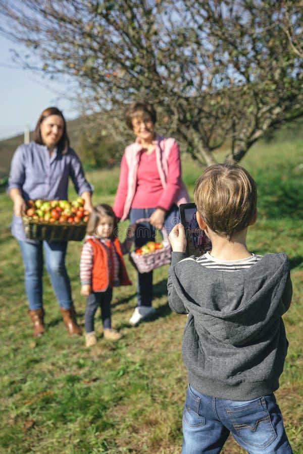 Muchacho que lleva la foto la familia con las manzanas en cesta fotografía de archivo libre de regalías