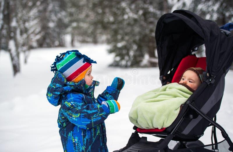 Muchacho que mira al bebé en un cochecito en un bosque Nevado fotografía de archivo
