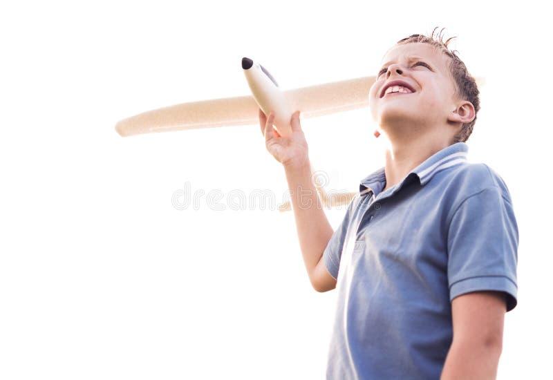 Muchacho que mira el cielo con un avión imagenes de archivo
