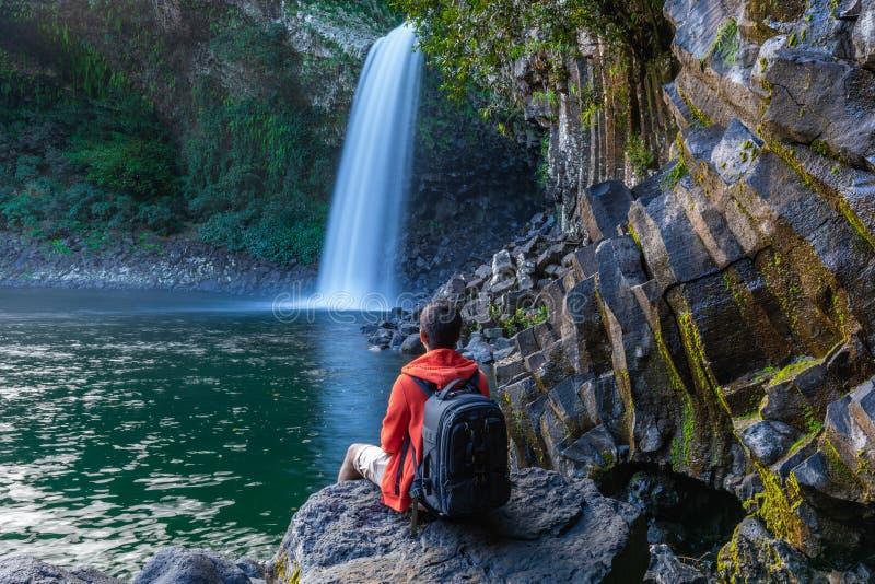 Muchacho que mira la cascada de Paix del La de Bassin en Reunion Island foto de archivo