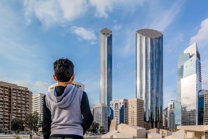 Muchacho que mira la ciudad de Abu Dhabi - arquitectura y rascacielos famosos del horizonte de Abu Dhabi con las nubes hermosas foto de archivo libre de regalías