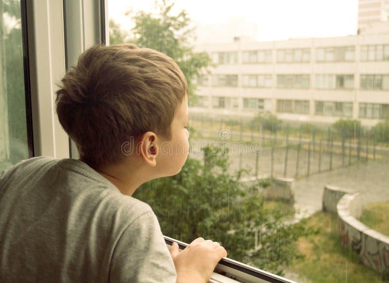 Muchacho que mira la lluvia a través de la ventana foto de archivo