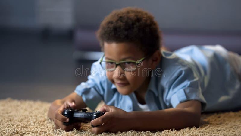 Muchacho que mira la pantalla mientras que juega al videojuego, daño de la salud, forma de vida sedentaria foto de archivo libre de regalías