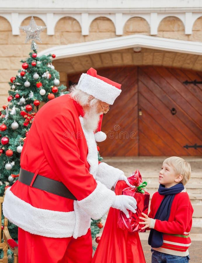 Muchacho que mira a Santa Claus While Taking Gift From fotografía de archivo