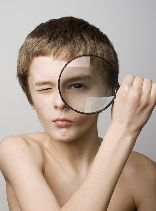 Muchacho que mira a través de la lente imagenes de archivo