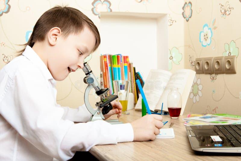 Muchacho que mira a través de un microscopio imagen de archivo