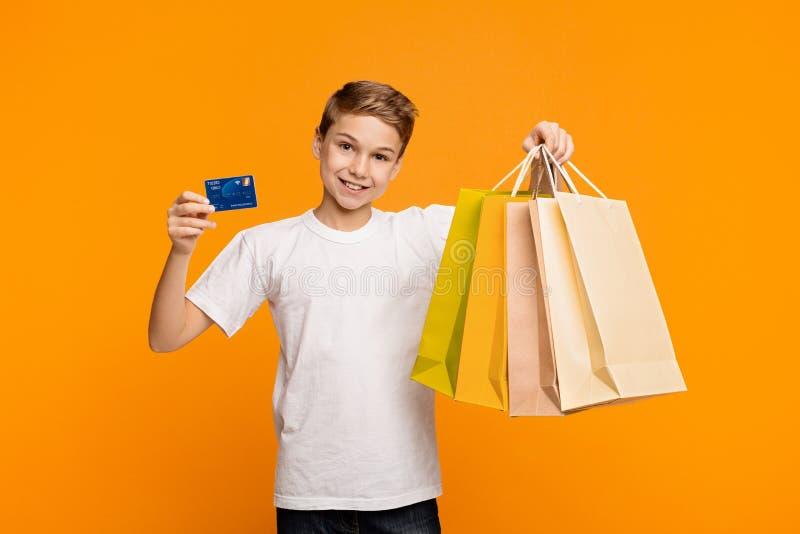 Muchacho que muestra bolsos de compras y crédito o tarjeta de débito imagen de archivo