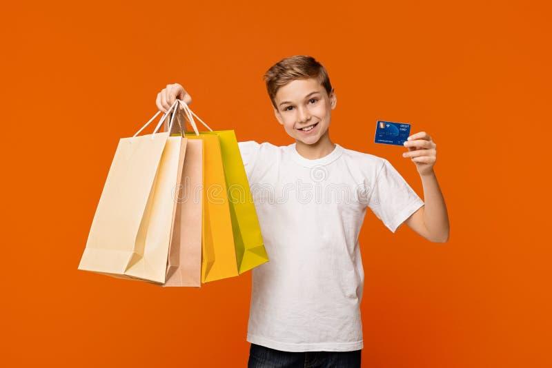 Muchacho que muestra sus bolsos que hacen compras y crédito o tarjeta de débito foto de archivo libre de regalías