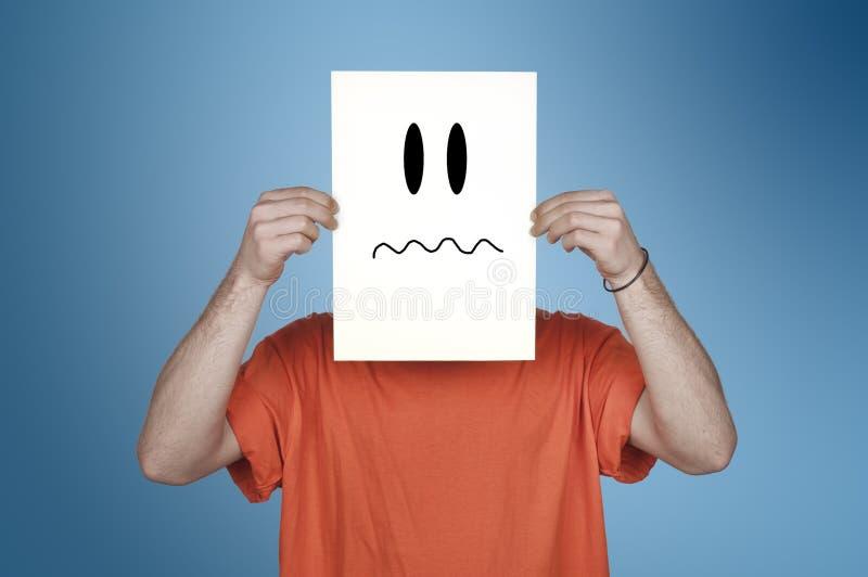 Muchacho que muestra un papel en blanco con un emoticon disgusted fotografía de archivo libre de regalías