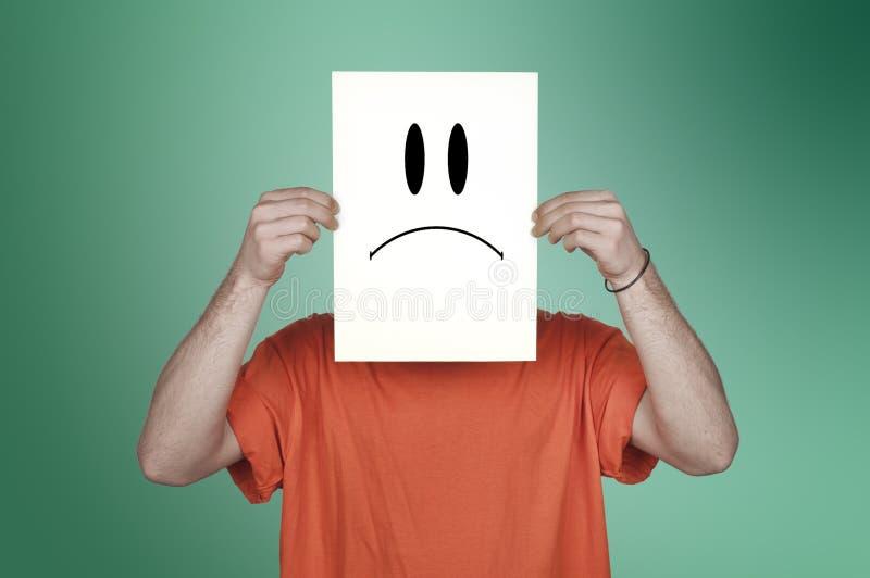 Muchacho que muestra un papel en blanco con un emoticon triste fotografía de archivo libre de regalías