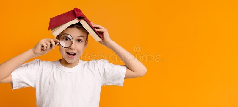 Muchacho que oculta debajo del libro y que mira a través de la lupa imagen de archivo libre de regalías