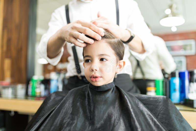 Muchacho que parece ausente mientras que peluquero Styling His Hair en tienda imágenes de archivo libres de regalías