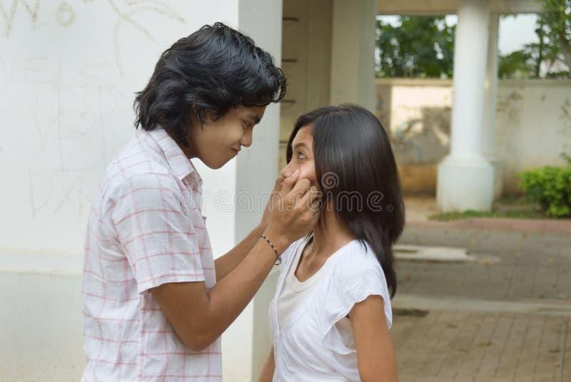 Muchacho que pellizca las mejillas de la muchacha imagenes de archivo