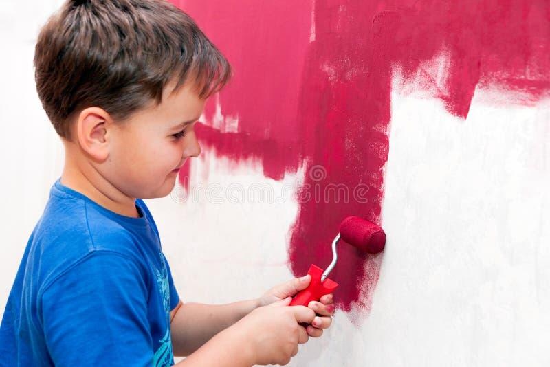 Muchacho que pinta la pared roja imágenes de archivo libres de regalías