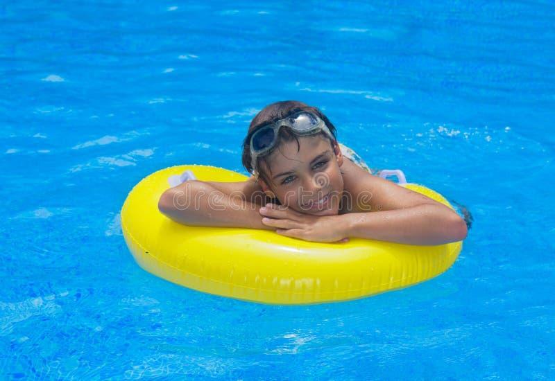 Muchacho que pone en el anillo de goma en piscina fotografía de archivo