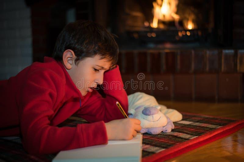 Muchacho que pone y que escribe una letra a Santa Claus fotos de archivo