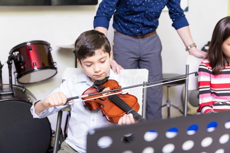 Muchacho que practica para ser un buen jugador del violín imagen de archivo