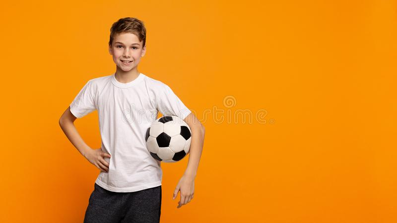 Muchacho que presenta con el balón de fútbol en fondo anaranjado del estudio foto de archivo