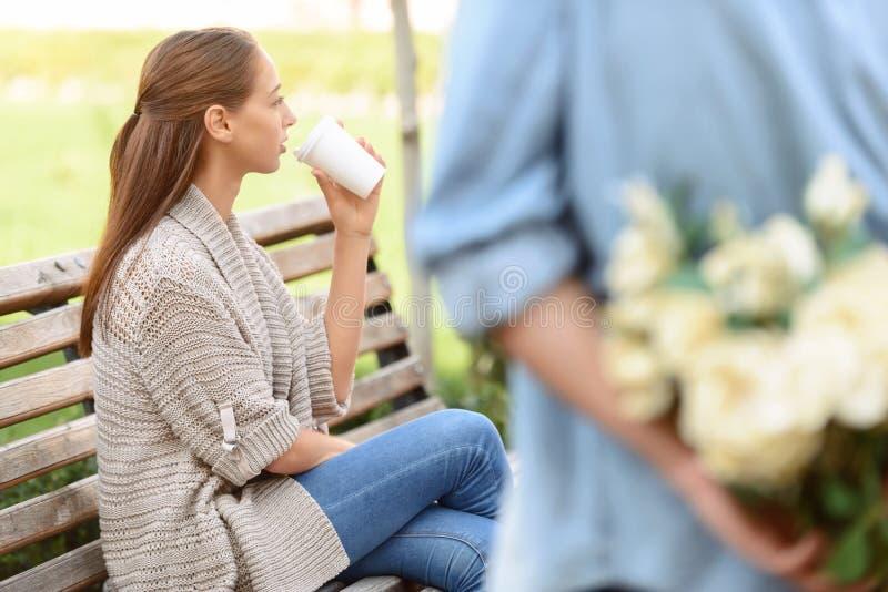 Muchacho que presenta las flores a la muchacha imagen de archivo libre de regalías