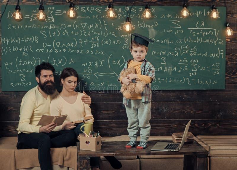 Muchacho que presenta su conocimiento a la mamá y al papá El niño elegante en casquillo graduado le gusta realizarse Padres que e imagen de archivo