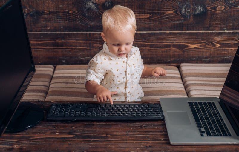 Muchacho que programa en el ordenador con los monitores y el ordenador portátil múltiples en el escritorio Programación que se co foto de archivo libre de regalías