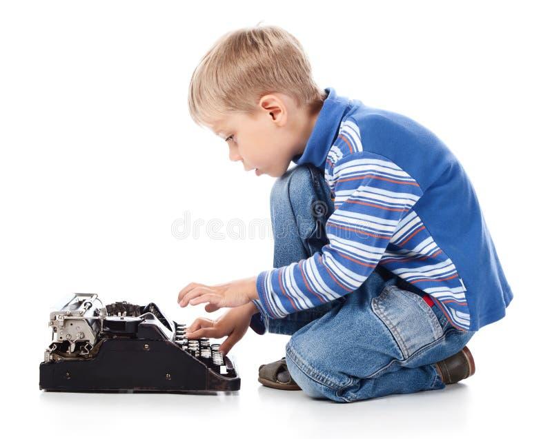 Muchacho que pulsa en la máquina de escribir vieja imagen de archivo libre de regalías