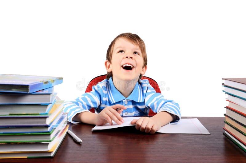 Muchacho que ríe mientras que se sienta en el escritorio foto de archivo