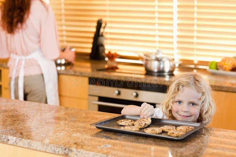 Muchacho que roba una galleta mientras que su madre no está mirando imagen de archivo libre de regalías