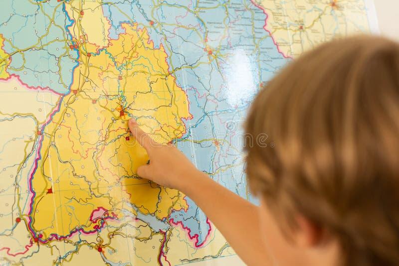 Muchacho que señala su finger en mapa del mundo en una sala de clase imagen de archivo libre de regalías