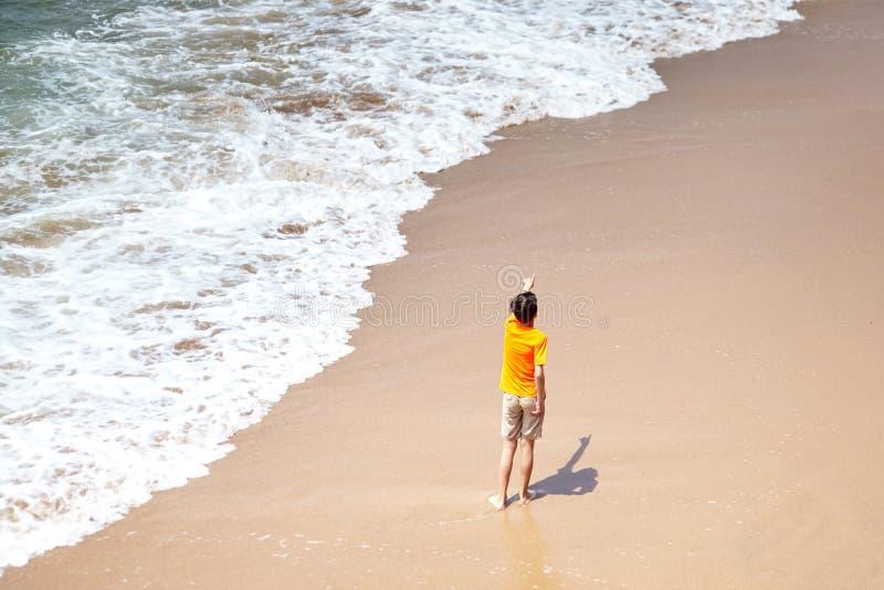 Muchacho que señala su mano lejos, niño que juega en una playa arenosa por la agua de mar imágenes de archivo libres de regalías