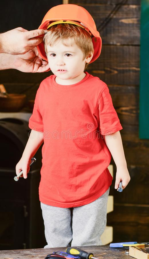 Muchacho que se coloca en taller de los papás El papá que sostiene el casco protector anaranjado sobre niños dirige Pequeño ingen imagen de archivo libre de regalías
