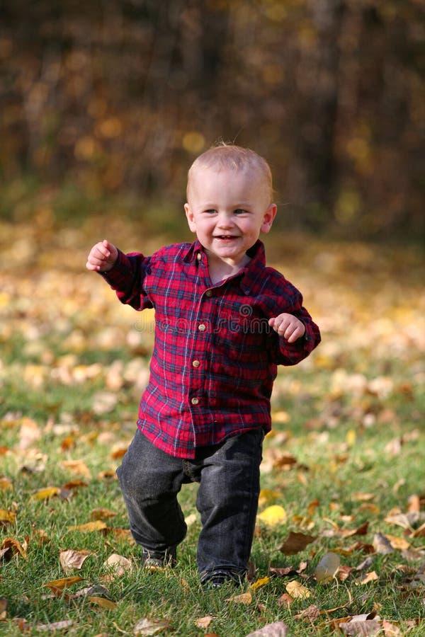 Muchacho que se ejecuta en hojas de otoño foto de archivo
