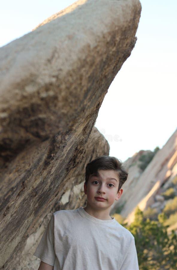 Muchacho que se inclina en roca imagen de archivo libre de regalías