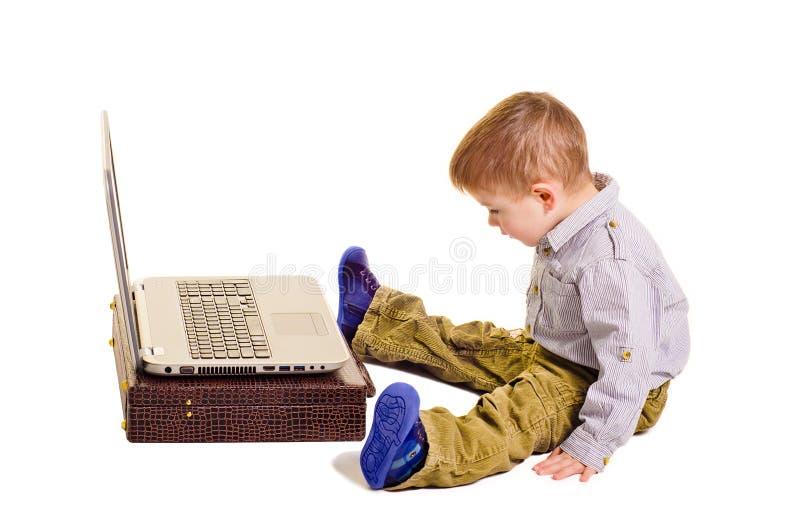 Muchacho que se sienta antes de un ordenador portátil fotos de archivo