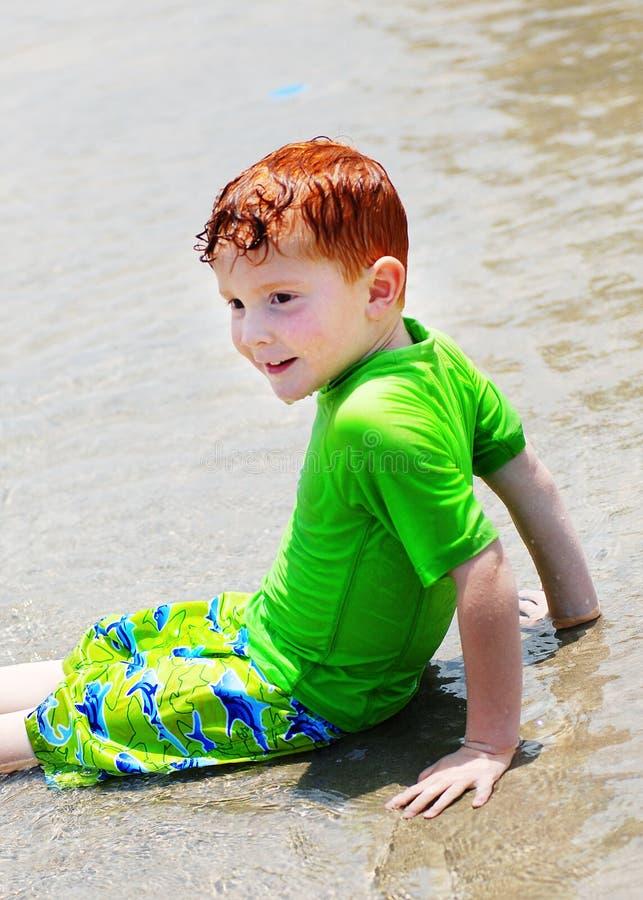 Muchacho que se sienta en agua baja fotos de archivo libres de regalías