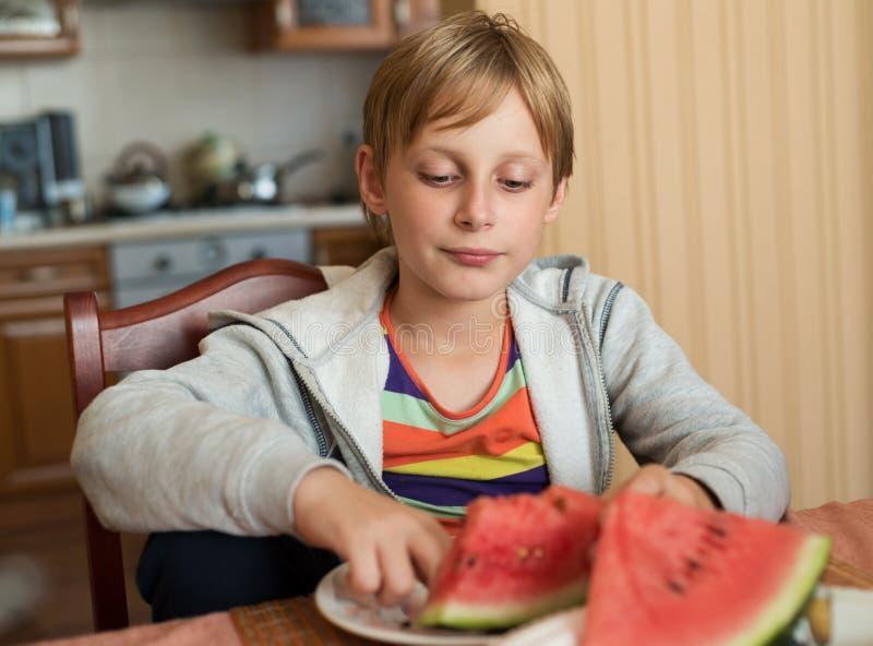Muchacho que se sienta en casa en la tabla y que come la sandía fotos de archivo libres de regalías