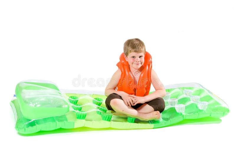 Muchacho que se sienta en el colchón de la playa imagen de archivo