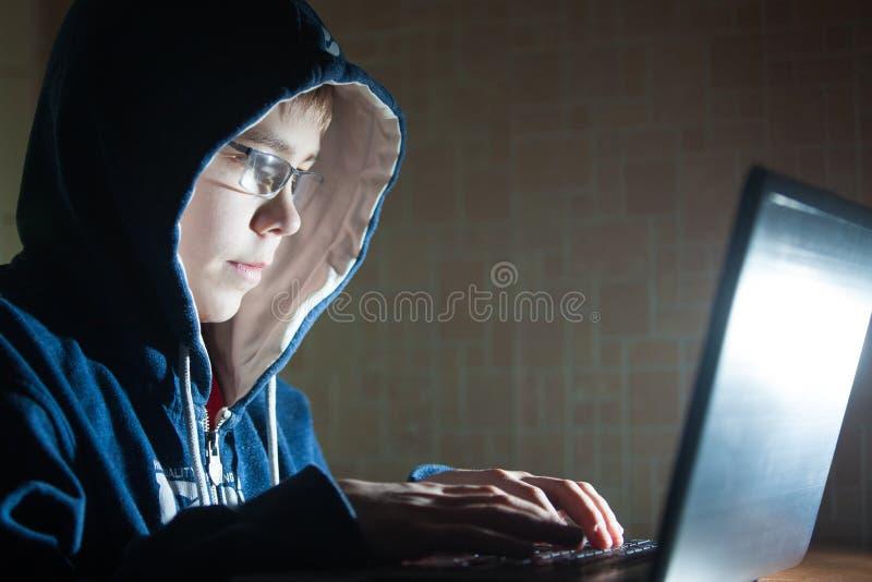 Muchacho que se sienta en el ordenador portátil foto de archivo
