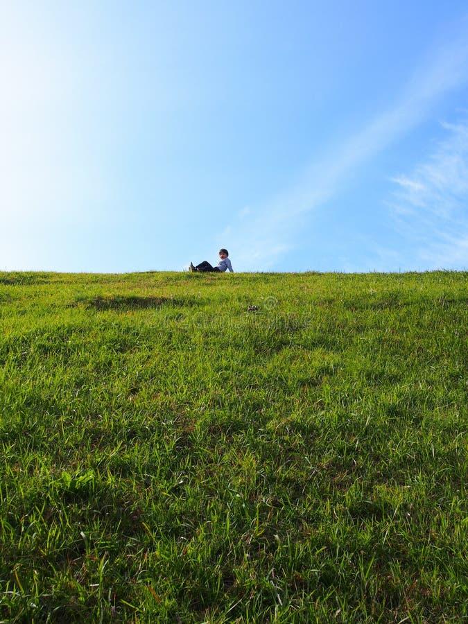 Muchacho que se sienta en la colina de la hierba imagen de archivo