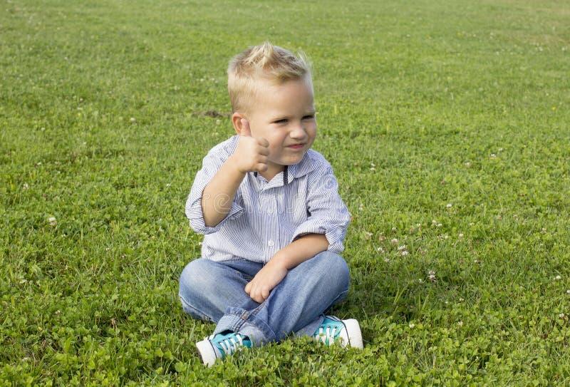 Muchacho que se sienta en la hierba imagen de archivo libre de regalías