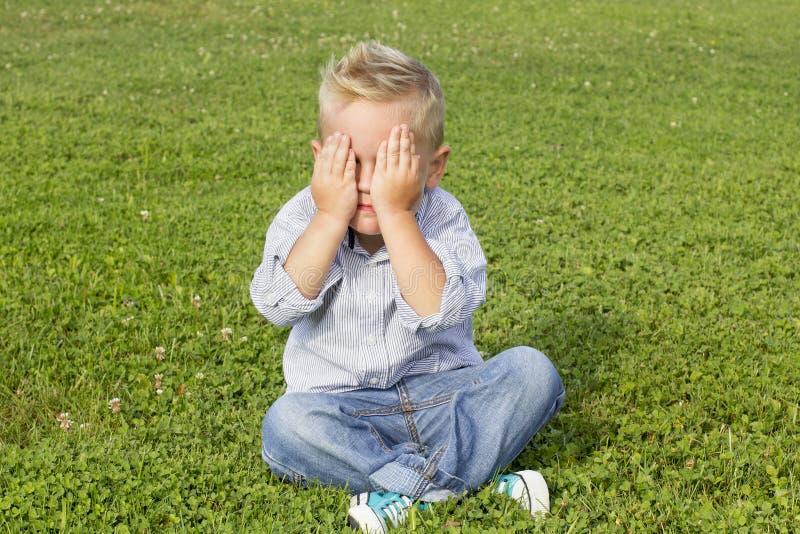 Muchacho que se sienta en la hierba fotografía de archivo