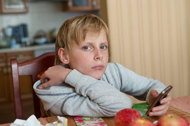 Muchacho que se sienta en la tabla en casa con el teléfono imágenes de archivo libres de regalías