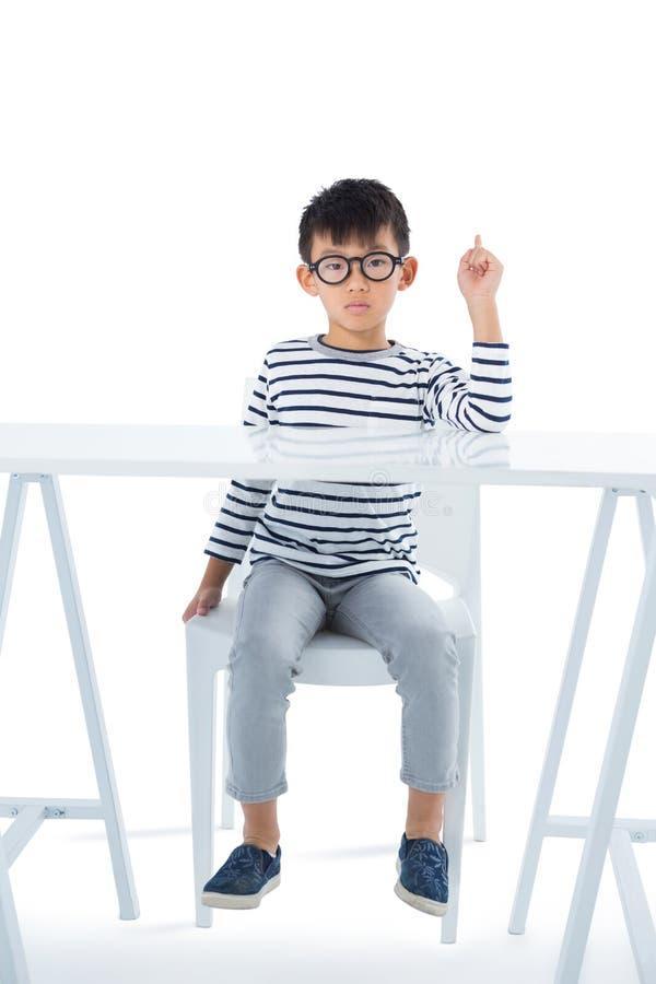 Muchacho que se sienta en silla contra el fondo blanco foto de archivo